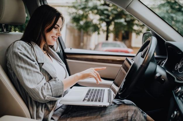 Zakenvrouw met een laptop in haar auto in de straat