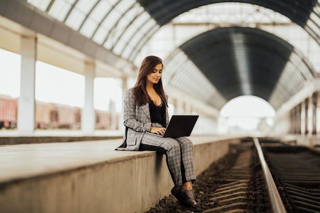 Zakenvrouw met een laptop op het perron van een treinstation.