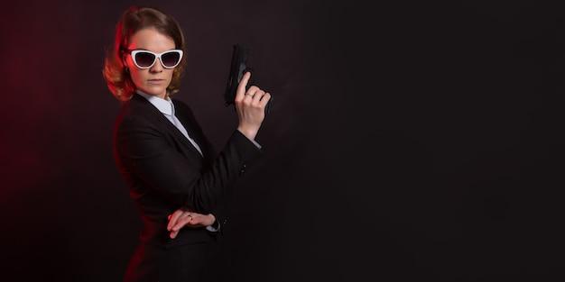 Zakenvrouw met een pistool in zijn hand. portret op een zwarte muur.