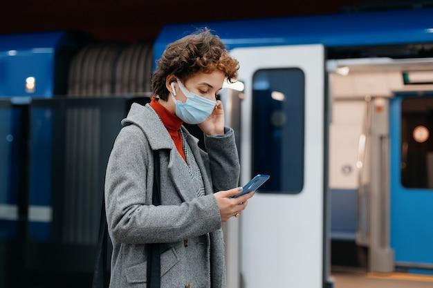 Zakenvrouw met een smartphone die in een metrotrein loopt