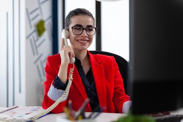 Zakenvrouw met een telefoondekking met financieel adviseur