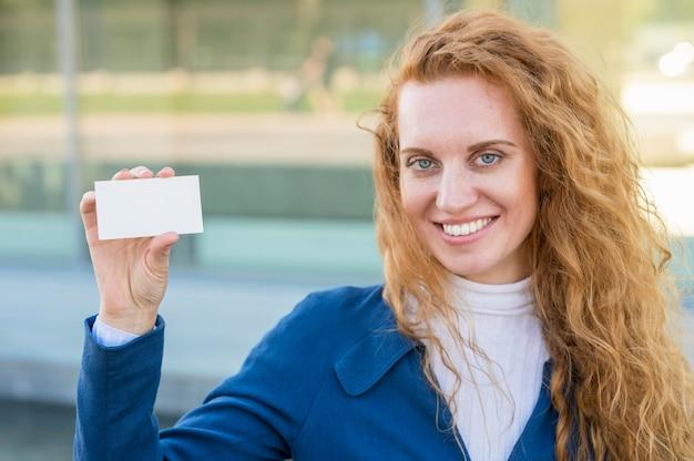 Zakenvrouw met een visitekaartje en glimlacht