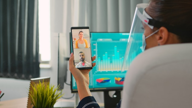 Zakenvrouw met gezichtsbescherming tegen coronavirus die videogesprek voert met een team op afstand op smartphone in een nieuw normaal kantoor. freelancer werkzaam in een financieel bedrijf met respect voor sociale afstand