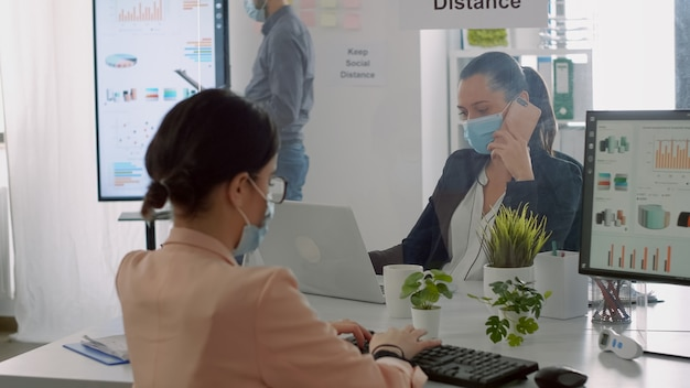 Zakenvrouw met gezichtsmasker die financiële rapporten controleert terwijl haar collega aan de telefoon zit in het kantoor van het bedrijf. collega's die sociale afstand bewaren om virusziekte te voorkomen