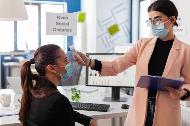 Zakenvrouw met gezichtsmasker die lichaamstemperatuur meet van collega in bedrijfskantoor met behulp van digitale thermometer met infrarood, tijdens wereldwijde pandemie met coronavirus, met behoud van sociale afstand.