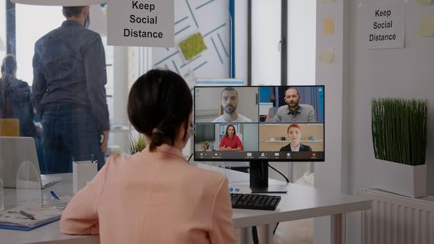 Zakenvrouw met gezichtsmasker in gesprek met team over communicatieproject tijdens online videocall-vergadering. uitvoerende freelancer zit aan bureautafel in nieuw normaal kantoor