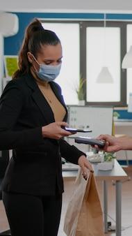Zakenvrouw met gezichtsmasker tegen coronavirus die afhaalmaaltijden betaalt met contactloze telefoon