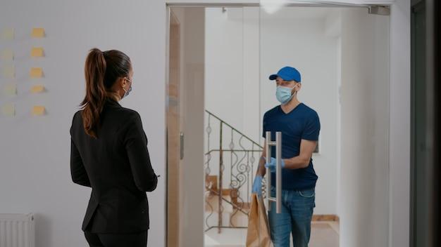 Zakenvrouw met gezichtsmasker tegen coronavirus die afhaalmaaltijden betaalt