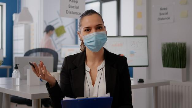 Zakenvrouw met gezichtsmasker tijdens online webinternet videogesprek met extern team. freelancer met communicatievergadering in nieuw normaal kantoor op videogesprekconferentie zoomvergadering tijdens pandemie