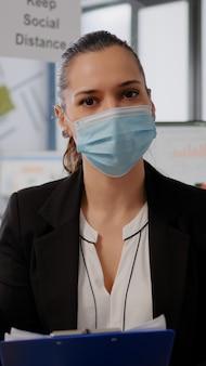 Zakenvrouw met gezichtsmasker tijdens online webinternet videogesprek met extern team