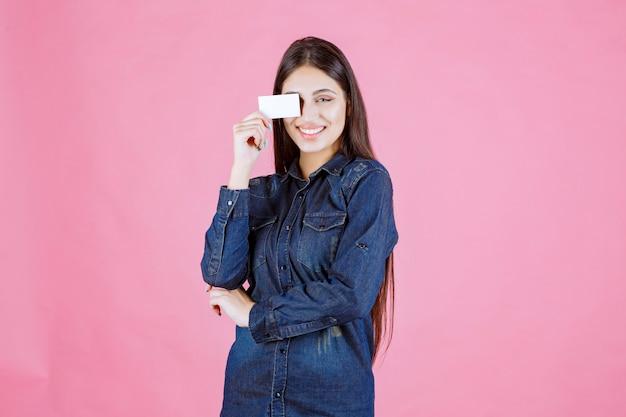 Zakenvrouw met haar visitekaartje aan haar oog