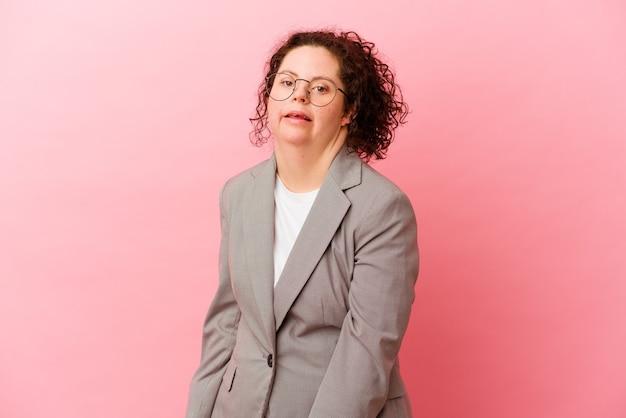 Zakenvrouw met het syndroom van down geïsoleerd op roze achtergrond kijkt opzij glimlachend, vrolijk en aangenaam.