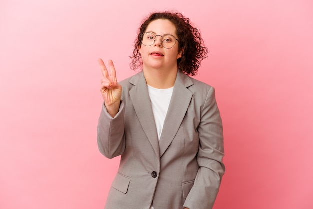 Zakenvrouw met het syndroom van down geïsoleerd op roze vrolijk en zorgeloos met een vredessymbool met vingers.