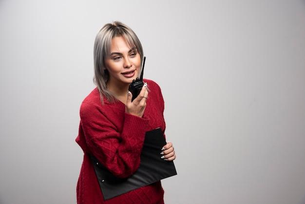 Zakenvrouw met klembord en radio transceiver poseren op grijze achtergrond.