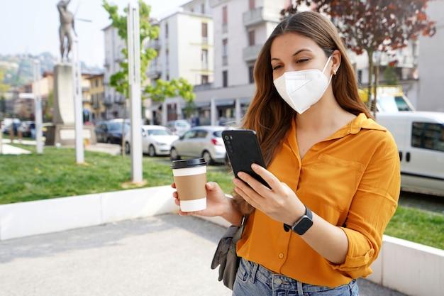 Zakenvrouw met kn95 ffp2-gezichtsmasker met smartphone houdt papieren koffiekopje in stadsstraat