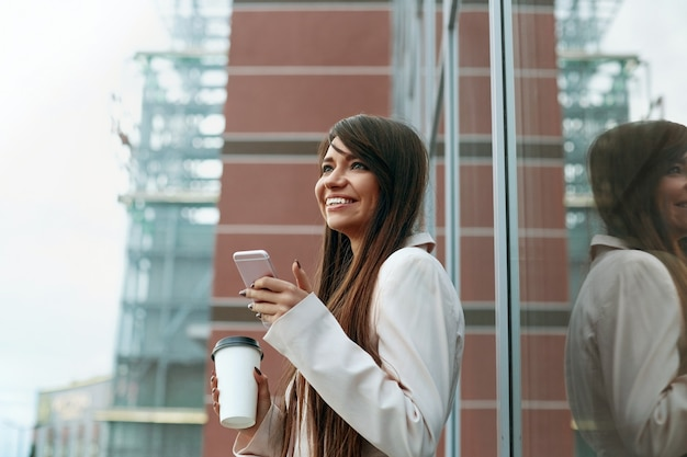 Zakenvrouw met koffie en praten over de telefoon in de buurt van kantoor