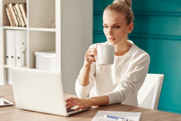 Zakenvrouw met koffie met behulp van laptop