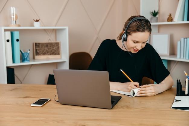 Zakenvrouw met koptelefoon op zit aan bureau en kijkt naar laptop die thuis aantekeningen maakt