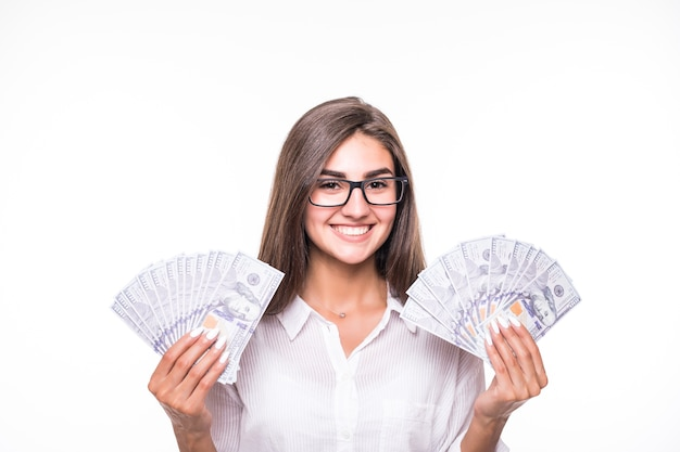 Zakenvrouw met lang bruin haar in vrijetijdskleding houdt veel bankbiljetten over wit