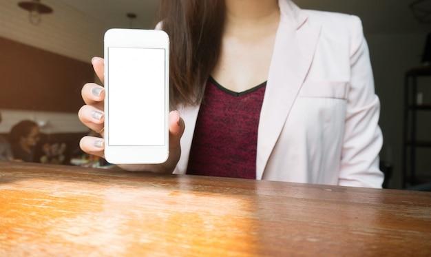 Zakenvrouw met leeg slimme telefoon scherm. meisje met behulp van slimme telefoon in cafe.
