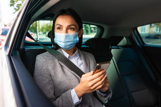 Zakenvrouw met medisch masker en smartphone in de auto