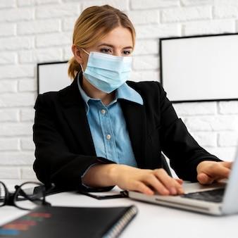 Zakenvrouw met medisch masker op kantoor met laptop werken