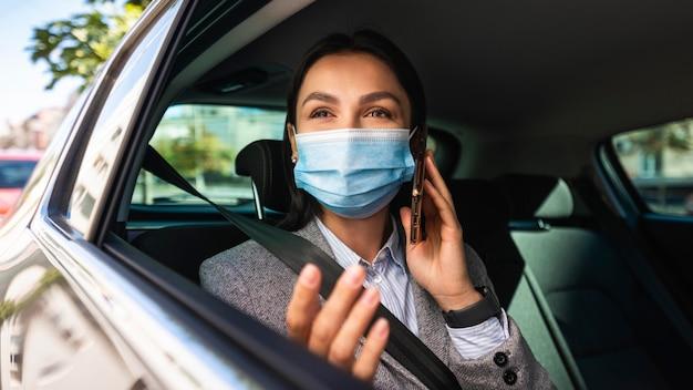 Zakenvrouw met medisch masker praten aan de telefoon in de auto