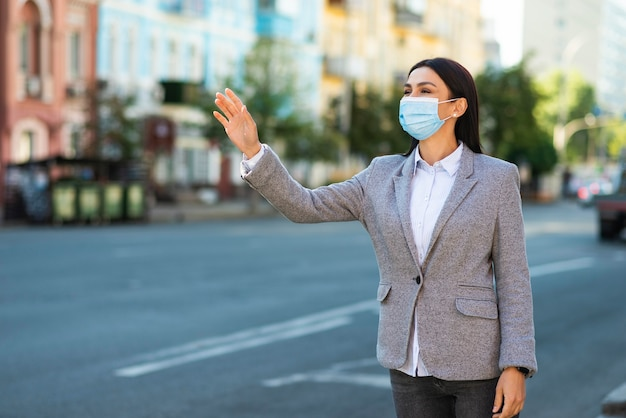 Zakenvrouw met medisch masker zwaaien in de straat