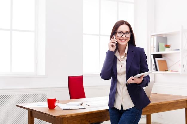 Zakenvrouw met mobiele telefoon schrijven van notities