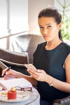 Zakenvrouw met mobiele telefoon zitten in het café