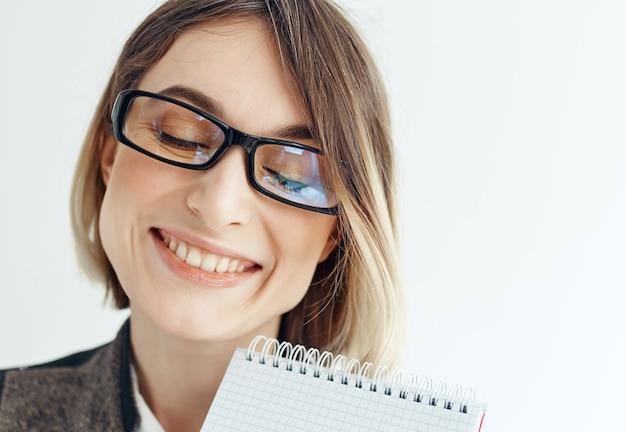Zakenvrouw met notitieblok in handen kantoor lichte achtergrond kopie ruimte