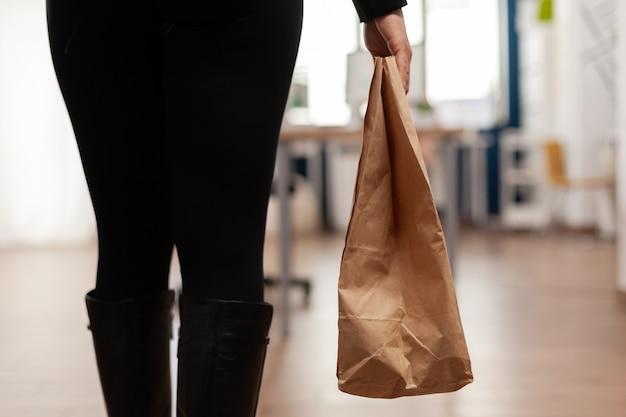 Zakenvrouw met papieren zak met afhaalmaaltijden maaltijdbestelling op bureau zetten