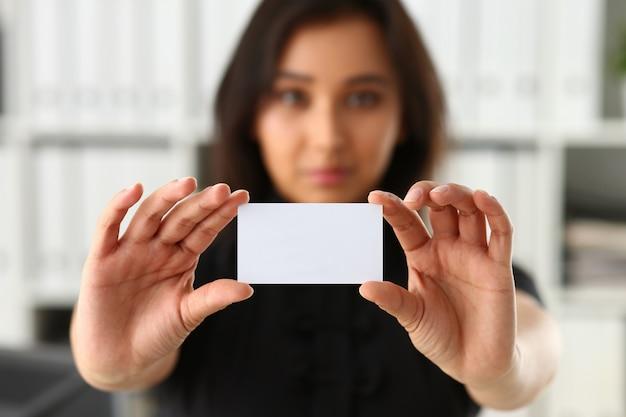 Zakenvrouw met persoonlijke kaart terwijl hij in kantoor staat