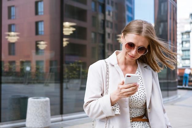 Zakenvrouw met telefoon in de buurt van kantoor portret van mooi lachend meisje in modieuze lichte kantoor...