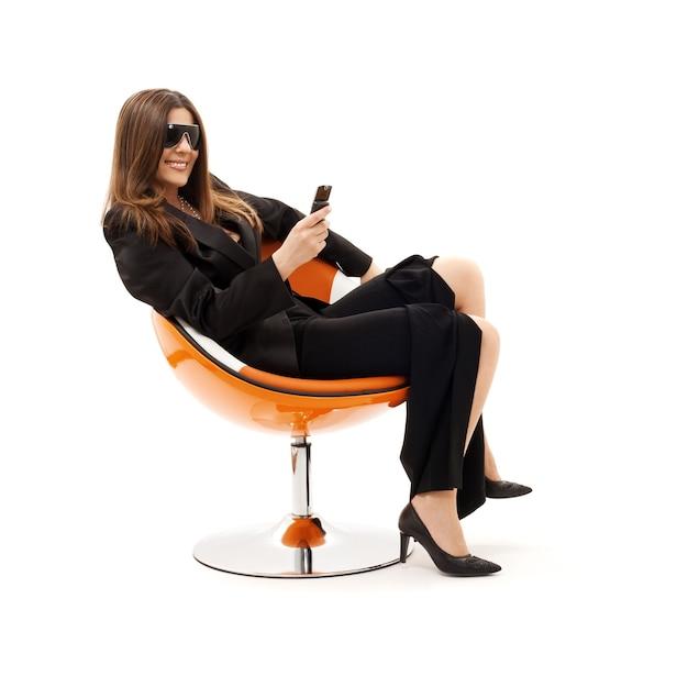 Zakenvrouw met telefoon in oranje stoel over wit