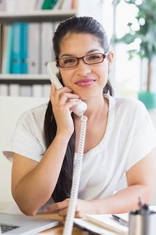 Zakenvrouw met vaste telefoon op kantoor