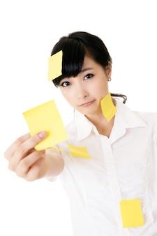 Zakenvrouw met veel gele memonota over haar lichaam
