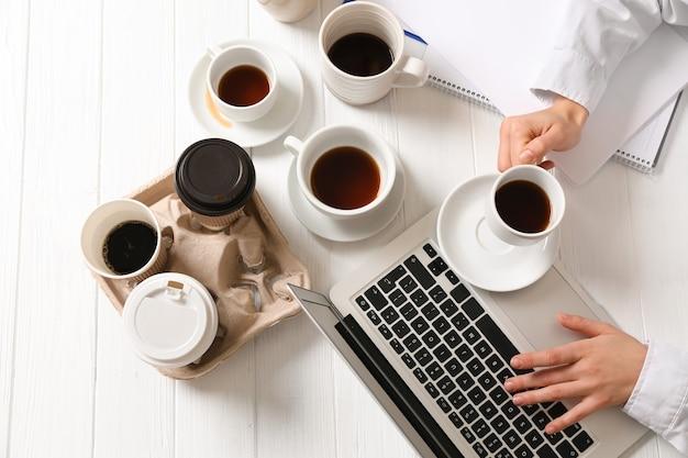 Zakenvrouw met veel lege kopjes koffie werken aan tafel. begrip verslaving