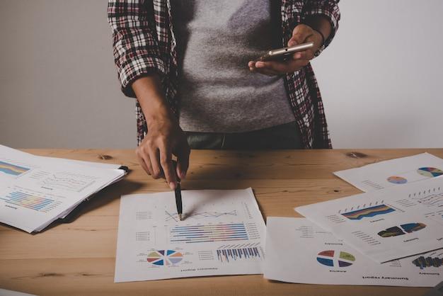Zakenvrouw met werkanalyse bedrijfsdocument grafiek en grafiek tijdens het gebruik van de telefoon met de klant.