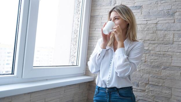 Zakenvrouw met witte kop koffie kijkt uit het raam - bakstenen muur