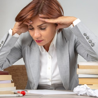 Zakenvrouw moe op kantoor en bezorgd in emoties. stress en hoofdpijn