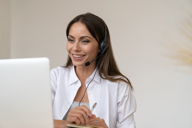 Zakenvrouw neemt deel aan videoconferentie, draagt een koptelefoon die communiceert met de klant