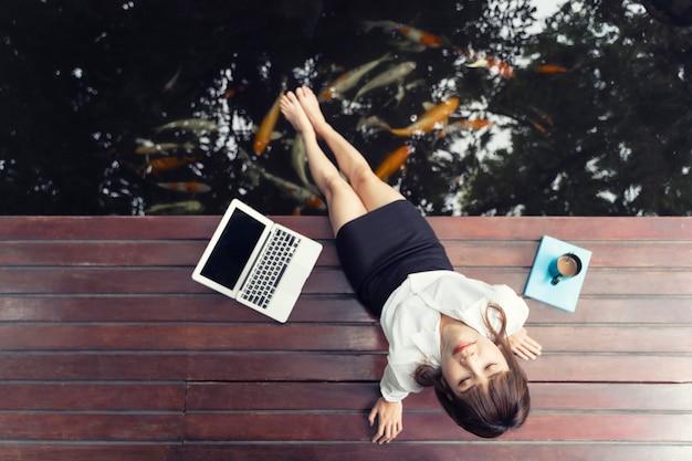 Zakenvrouw neemt een rust met ontspannen op het balkon en de karper vijver.