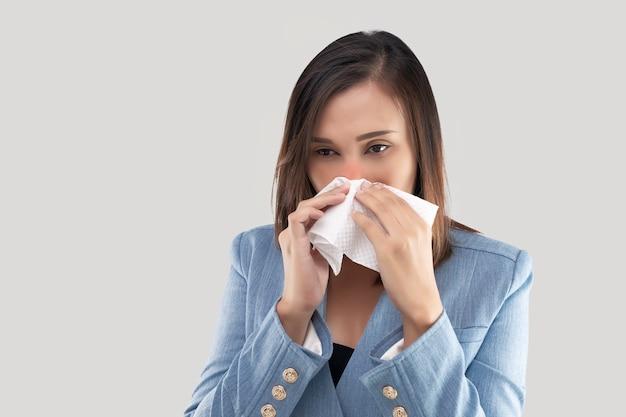 Zakenvrouw neus brandend gevoel vanwege het stof in de lucht