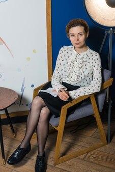 Zakenvrouw of journalist werken in moderne kantoren, zittend op de fauteuil, met laptop
