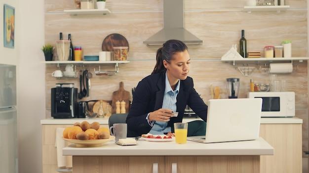Zakenvrouw online betalen met creditcard op een laptop tijdens het ontbijt. online winkelen voor goederen en kleding, moderne technologie gebruiken in het dagelijks leven, betalen via internet