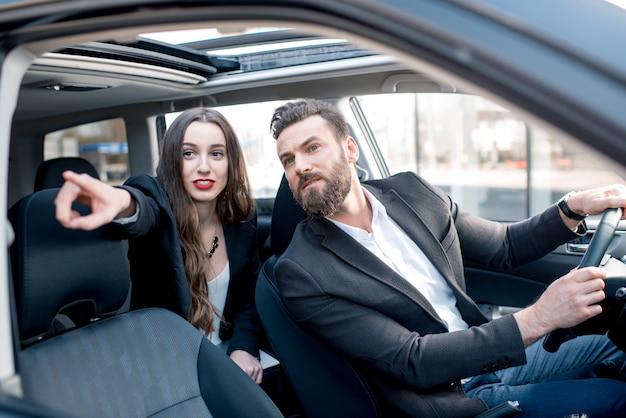 Zakenvrouw op de achterbank met elegante man autorijden in de stad. bezorgd over een vertraging bij een belangrijke vergadering