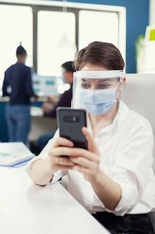 Zakenvrouw op de werkplek aan het chatten met een smartphone met een gezichtsmasker tegen covid19. multi-etnische collega's die werken met respect voor sociale afstand in een financieel bedrijf.