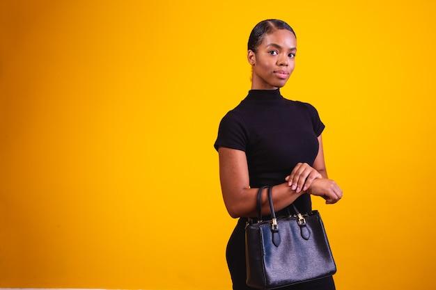 Zakenvrouw op gele achtergrond die zwarte kleding en handtas draagt.