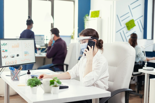 Zakenvrouw op kantoor met gezichtsmasker tegen covid 19 met een gesprek op smartphone. multi-etnische collega's die werken met respect voor sociale afstand in een financieel bedrijf.